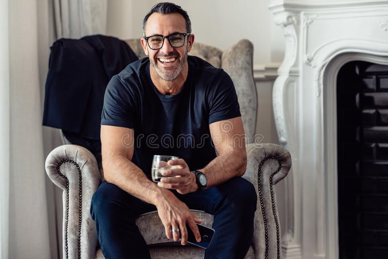 Portrait of smiling businessman sitting in hotel room with phone and glass of drink looking at camera. Mature man relaxing in stock photos