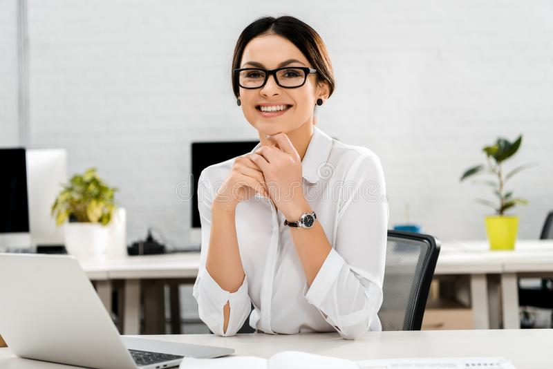 Portrait of smiling businesswoman in eyeglasses at workplace with laptop. In office stock photography