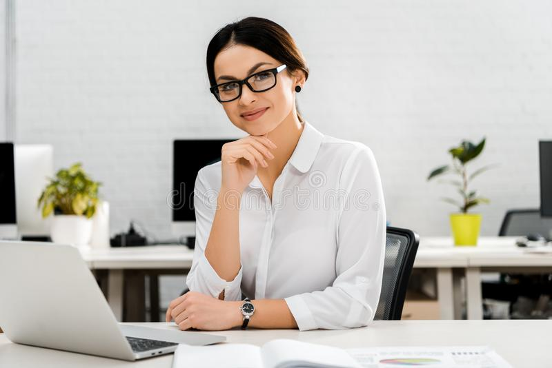 Portrait of smiling businesswoman in eyeglasses at workplace with laptop. In office stock photo
