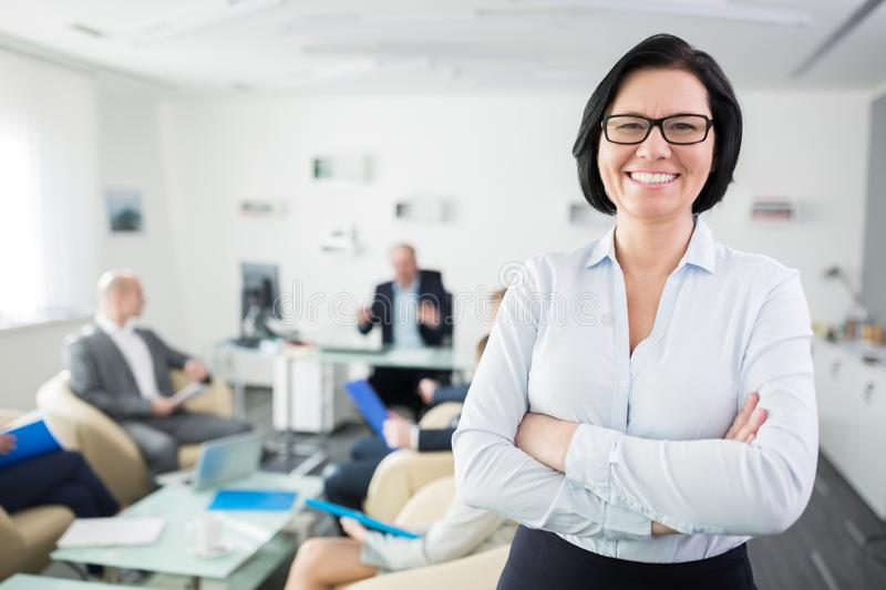 Smiling Businesswoman Standing Arms Crossed In Office royalty free stock image
