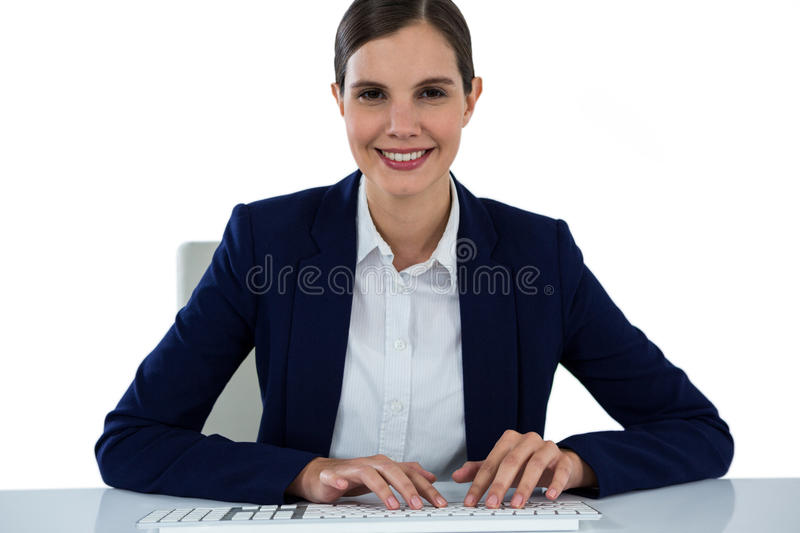 Portrait of smiling businesswoman typing on keyboard at desk stock photo