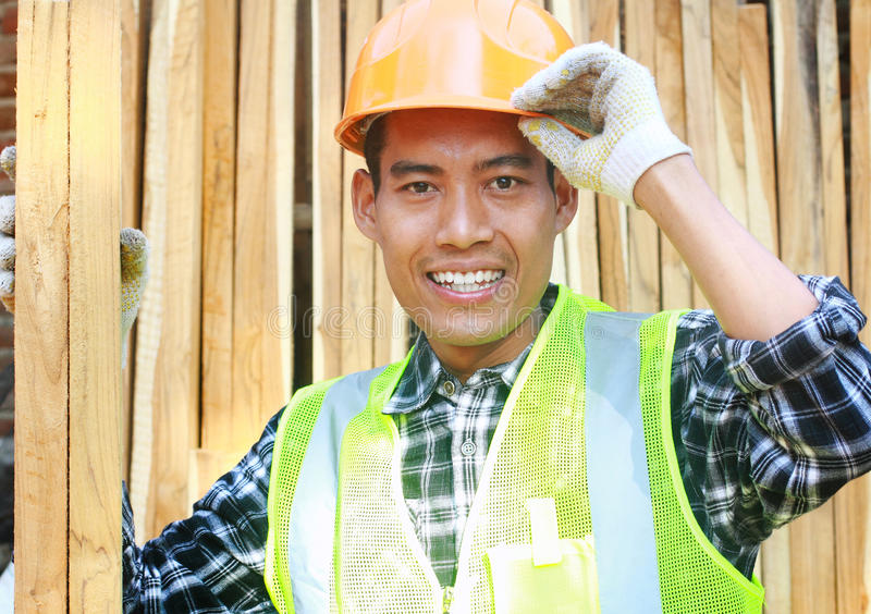 Portrait of a smiling carpenter holding wood royalty free stock image
