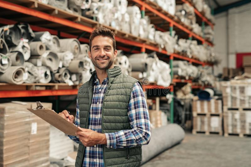Smiling worker doing inventory on a warehouse floor royalty free stock photography