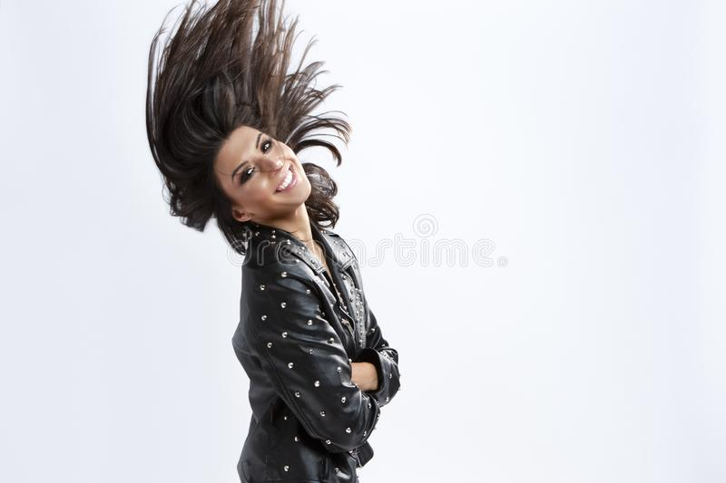 Portrait of Smiling Caucasian Brunette Girl in Rough Leather Jacket Making Waving Hair royalty free stock photography