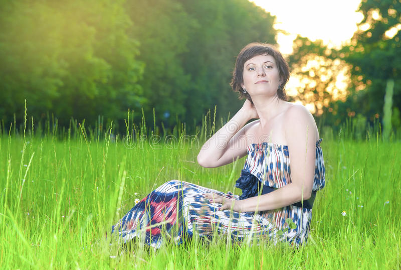 Portrait of Smiling Caucasian Brunette Woman Posing Outdoors on Nature Background at Sunset stock image