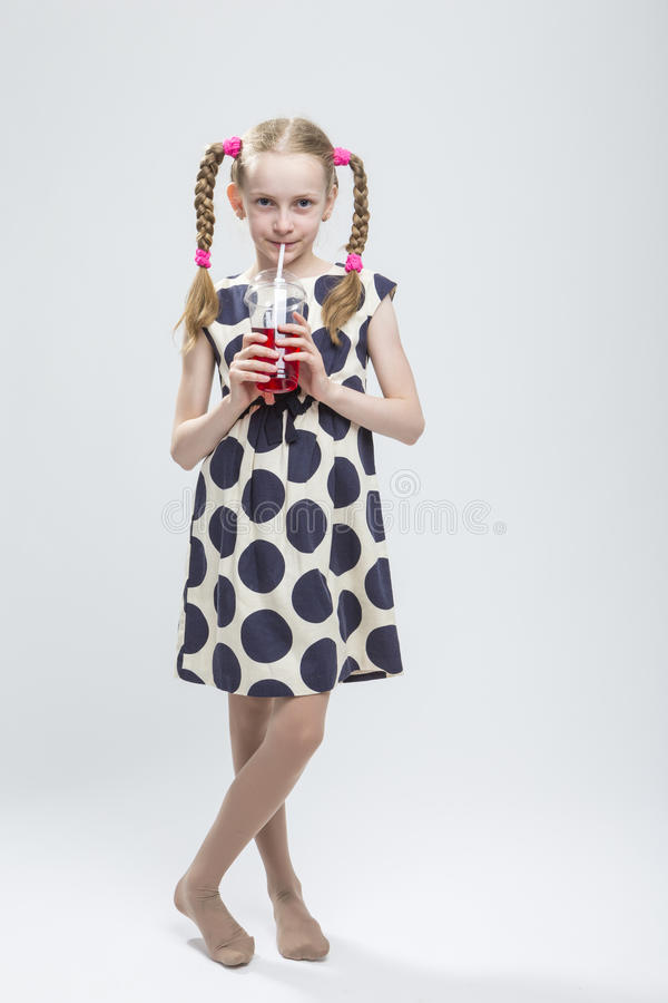Portrait Of Smiling Caucasian Little Girl With Pigtails Standing Barefoot in Polka Dot Dress royalty free stock image