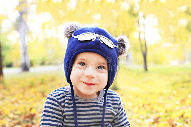 Happy smiling funny little boy wearing a cute hat outdoor in the autumn park. Happy childhood, dream, leisure concept royalty free stock photography