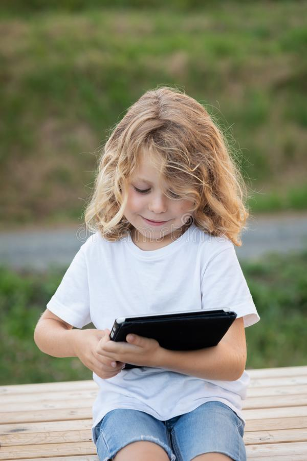 Portrait of smiling child with long hair holding a digital tablet stock photo