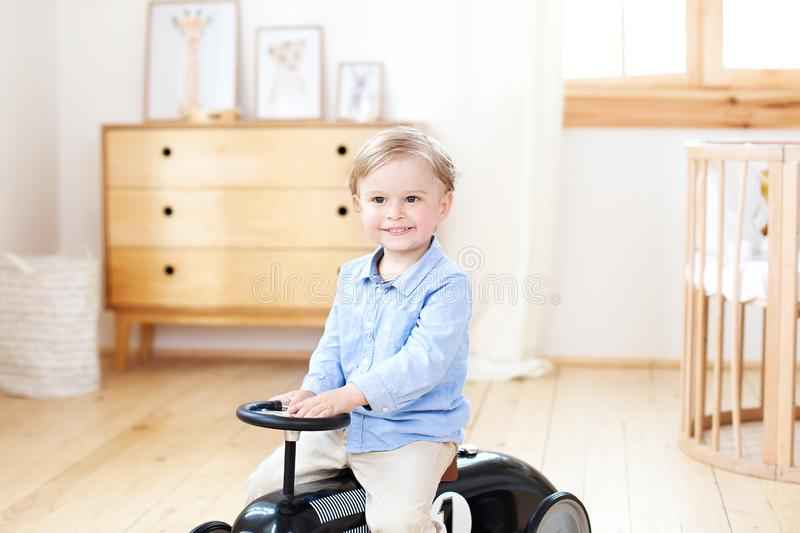 Portrait smiling  child riding toy vintage car. Funny kid playing at home. Summer vacation and travel concept. little boy driving stock photo