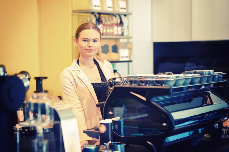 Portrait of smiling coffee shop owner standing behind counter while looking at camera royalty free stock photo