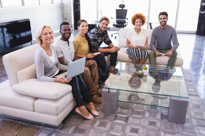 Portrait of smiling colleagues sitting on sofa stock photos