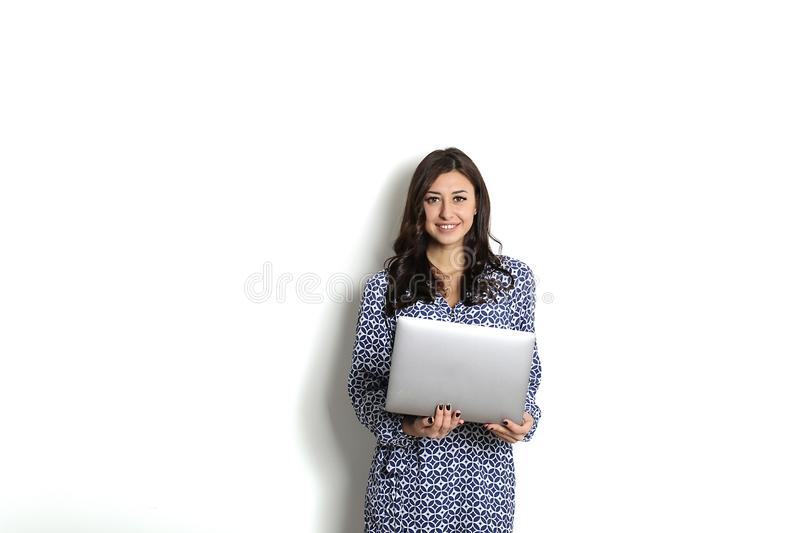 Portrait, smiling confident pretty woman long sleeve dress, holding grey laptop device and typing while standing against solid whi stock image