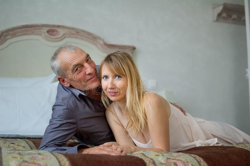 Portrait of Smiling Couple with Age Difference. Beautiful Young Woman with Her Senior Lover Lying on the Bed. Man. Kissing His Girlfriend royalty free stock image