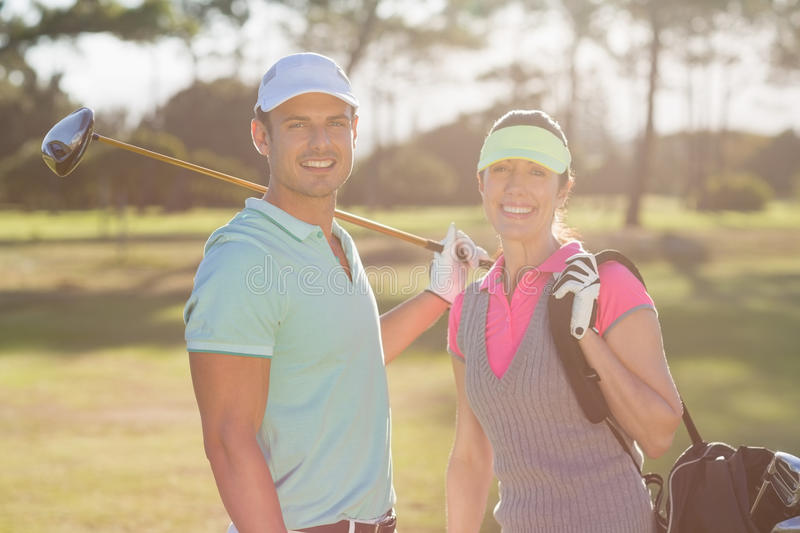 Portrait of smiling couple with bag and golf club stock photos