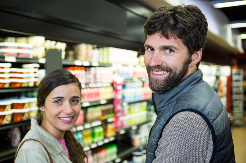 Portrait smiling couple in grocery section. At supermarket royalty free stock image
