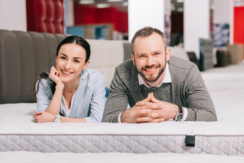 portrait of smiling couple lying on mattress stock photos