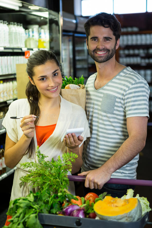 Portrait of smiling couple with notepad shopping for vegetables in organic section. Of supermarket royalty free stock image