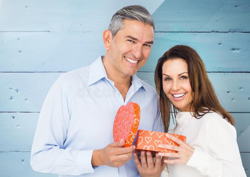 Portrait of smiling couple standing with gift box. Against wooden background royalty free stock image