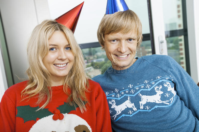 Portrait of smiling couple wearing Christmas sweaters and party hats in living room at home royalty free stock photos