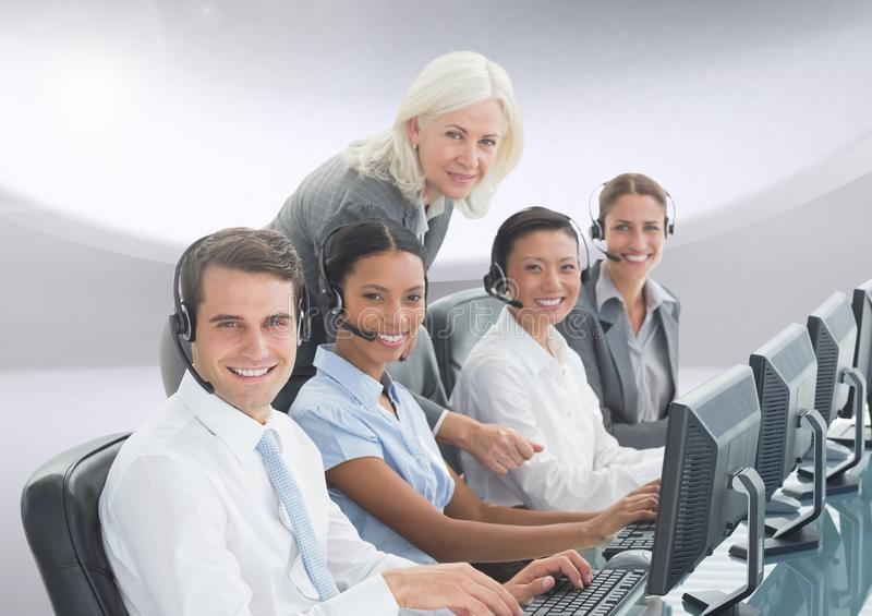Portrait of smiling customer service peoples with headphones working on computer stock images