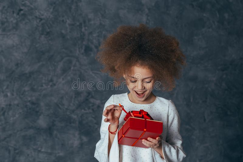 Portrait of a smiling cute girl with curly hair and a red gift in her hands. studio shot. Portrait of a smiling cute girl with curly hair and a red gift in her stock images