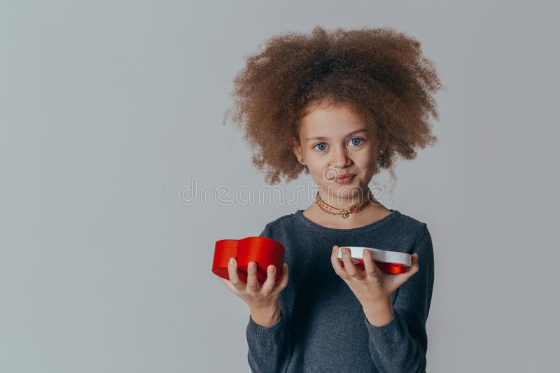 Portrait of a smiling cute girl with curly hair and a red gift in her hands. studio shot. Portrait of a smiling cute girl with curly hair and a red gift in her stock photo