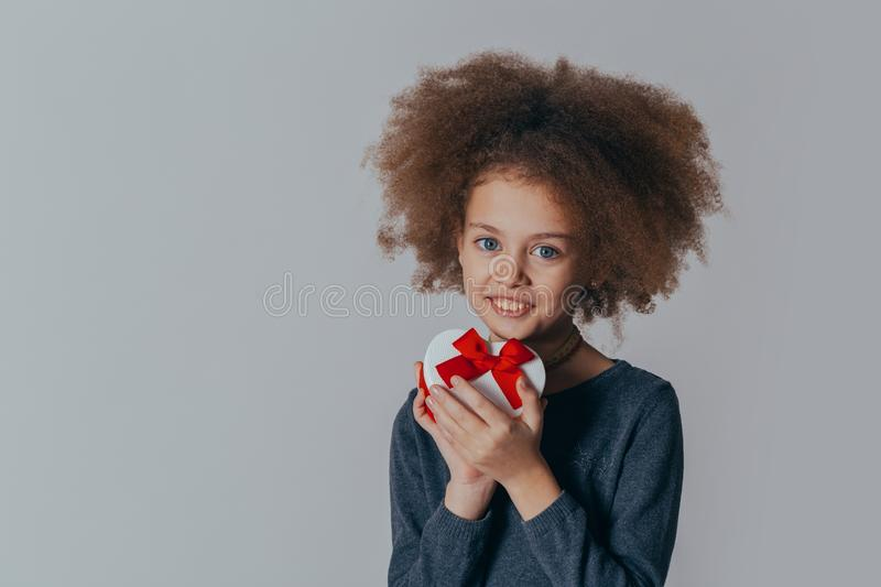 Portrait of a smiling cute girl with curly hair and a red gift in her hands. studio shot. Portrait of a smiling cute girl with curly hair and a red gift in her stock photography