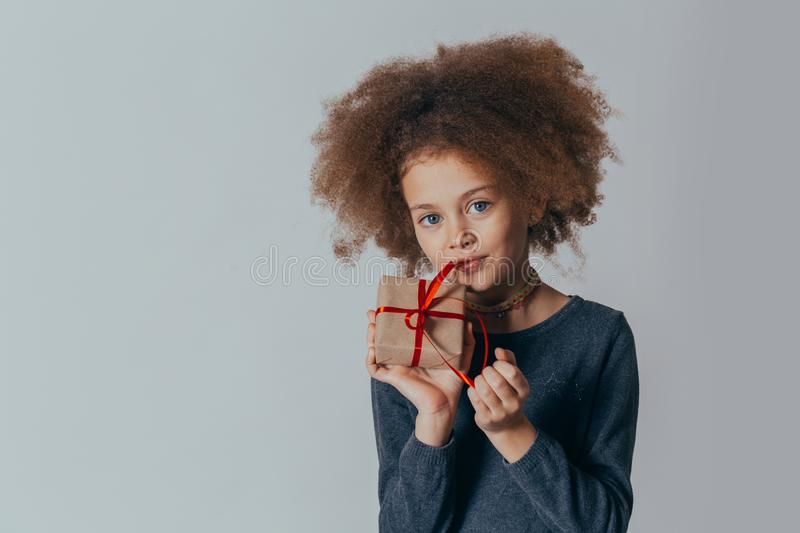 Portrait of a smiling cute girl with curly hair and a red gift in her hands. studio shot. Portrait of a smiling cute girl with curly hair and a red gift in her royalty free stock photo