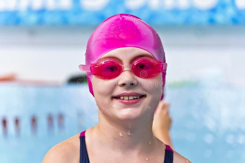 Girl in pink rubber hat. Portrait of smiling cute girl in swimming pool stock image