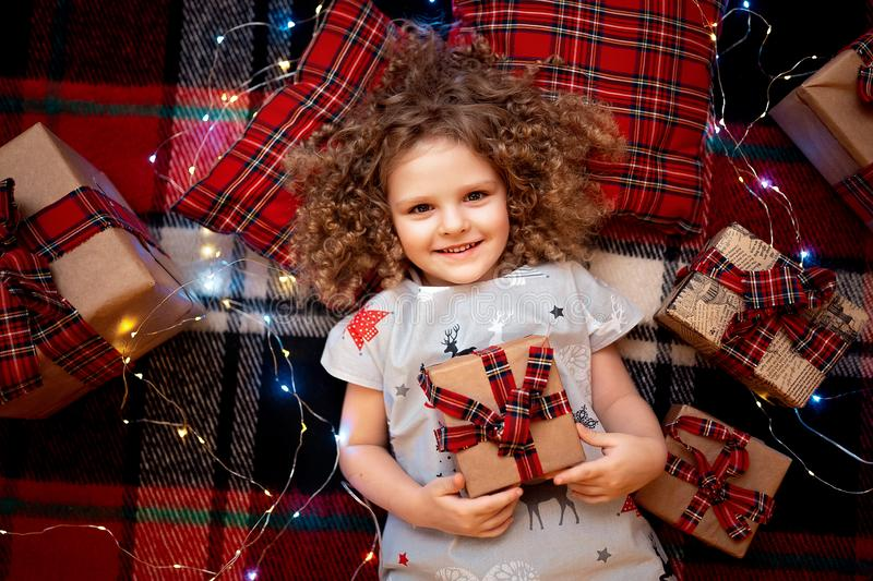 Portrait of smiling cute little child in holiday christmas pajamas holding gift box. Top view. stock images