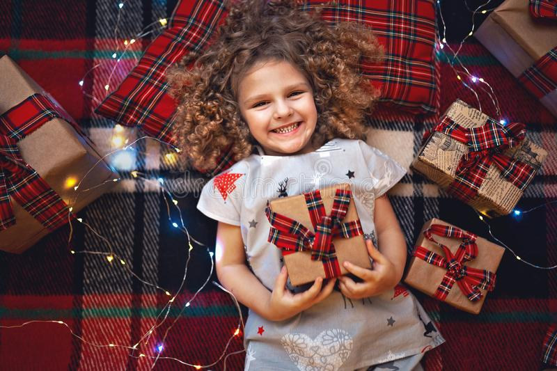 Portrait of smiling cute little child in holiday christmas pajamas holding gift box. Top view. royalty free stock photography