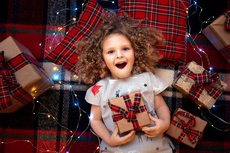 Portrait of smiling cute little child in holiday christmas pajamas holding gift box. Top view. stock photography