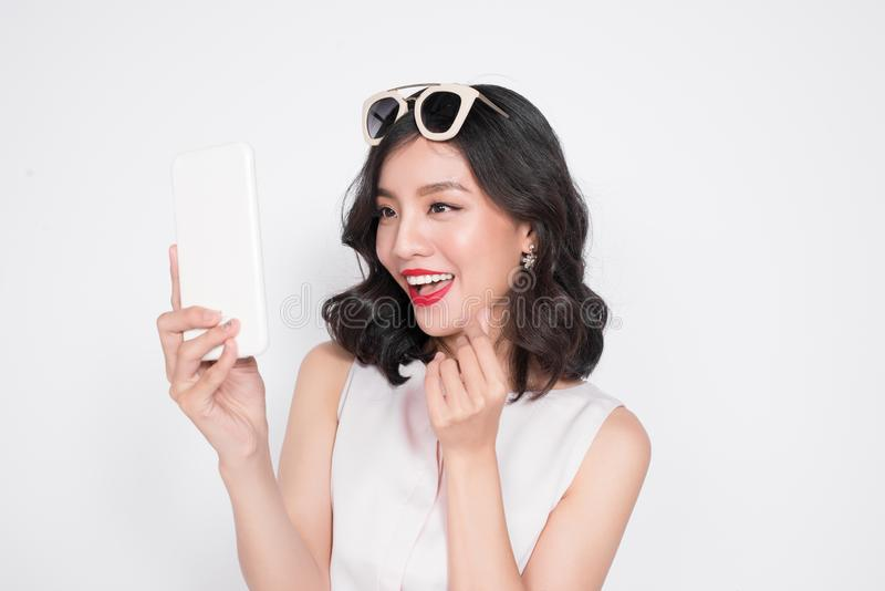 Portrait of a smiling cute woman making selfie photo on smartphone isolated on a white background stock photos