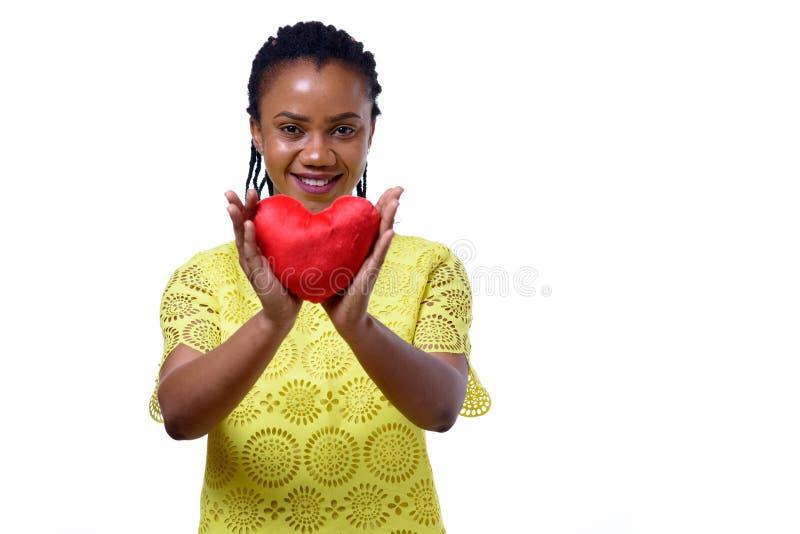 Smiling dark-skinned woman holding red heart. Portrait of smiling dark-skinned woman holding red heart against white background stock photos