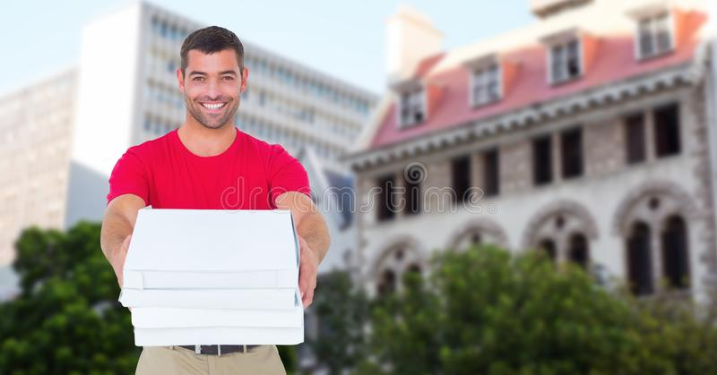 Portrait of smiling delivery man holding pizza boxes against buildings royalty free stock image
