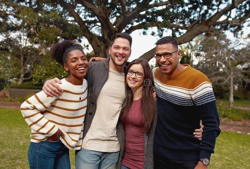 Portrait of a smiling diverse group of young friend enjoying in the park - colorful clothing - very happy royalty free stock photo