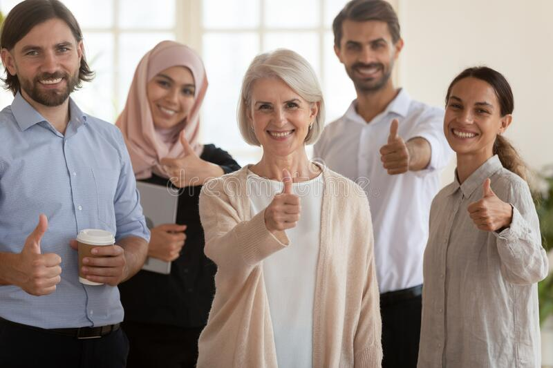 Happy multiethnic colleagues show thumbs up gather in office stock photo