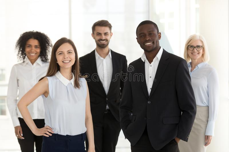 Portrait of smiling diverse work team standing posing in office stock photography