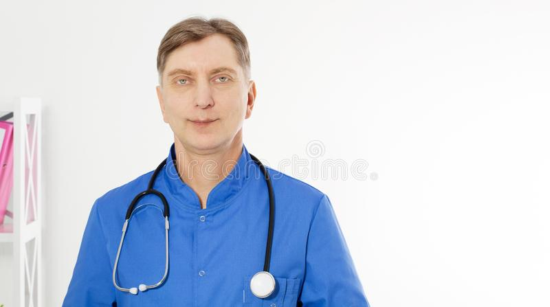 Portrait of Smiling doctor posing with the office, he is wearing a stethoscope, copy space for logo or text royalty free stock photography