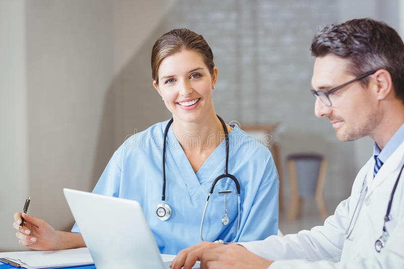 Portrait of smiling doctor sitting at desk with colleague royalty free stock photos