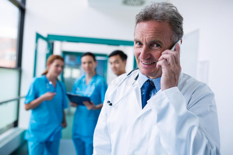 Portrait of smiling doctor talking on mobile phone in corridor. At hospital royalty free stock photography