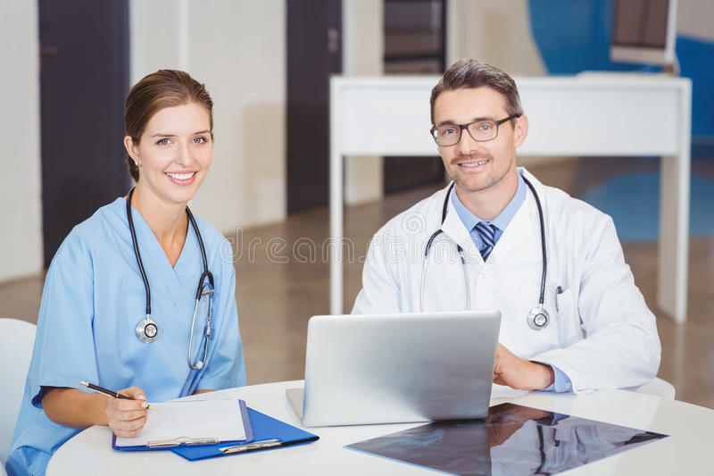 Portrait of smiling doctors sitting at desk royalty free stock photo