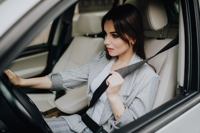 Portrait of smiling driver woman fastening her seatbelt before driving a car. royalty free stock photo