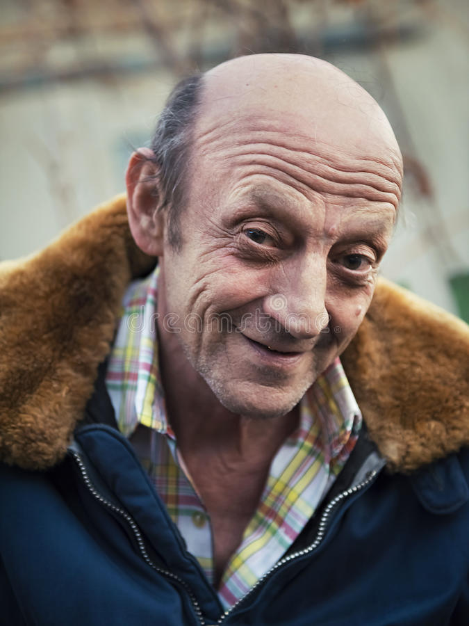 Portrait of a smiling elderly man outdoors closeup royalty free stock photo