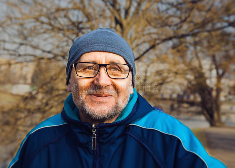 Portrait of a smiling elderly man wearing glasses, a gray hat an royalty free stock images