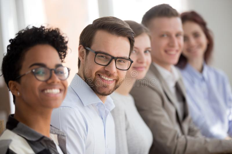 Portrait of smiling employees sit in row looking at camera stock photo