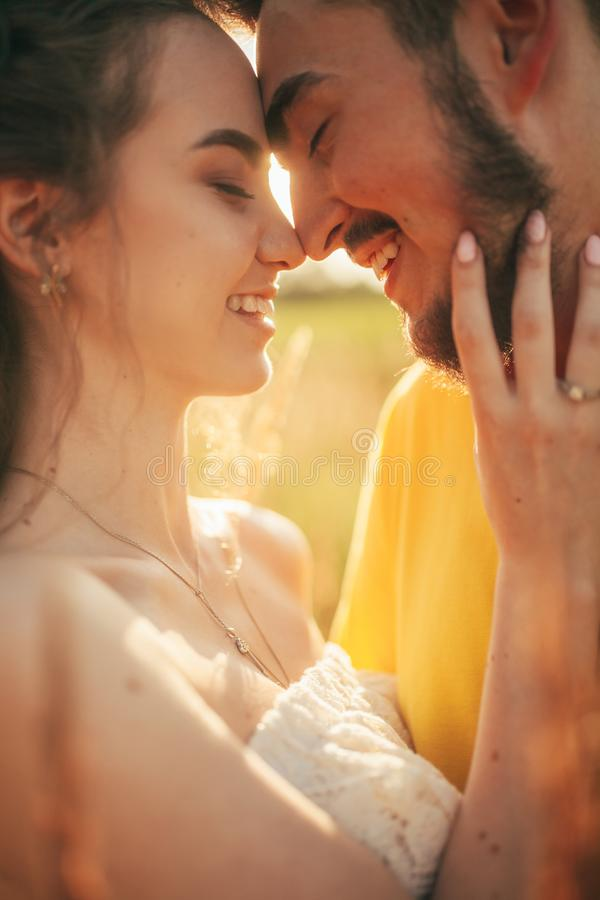 Portrait of smiling enamored couple at meadow. Backlit stock image