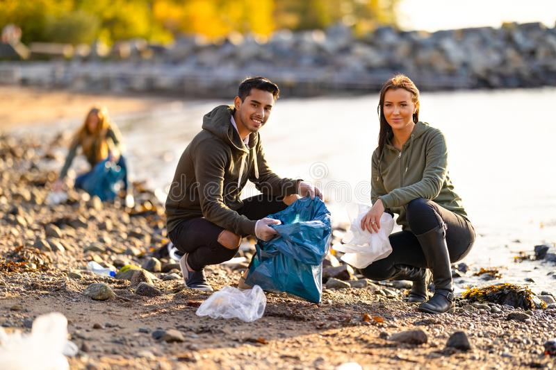 Portrait of smiling environmental protection volunteers cleaning beach royalty free stock images