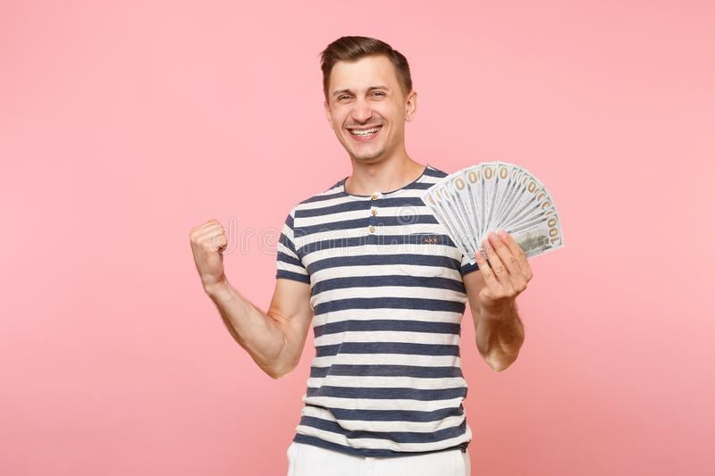 Portrait of smiling excited young man in striped t-shirt holding bundle lots of dollars, cash money, ardor gesture on. Copy space isolated on pink background royalty free stock photography