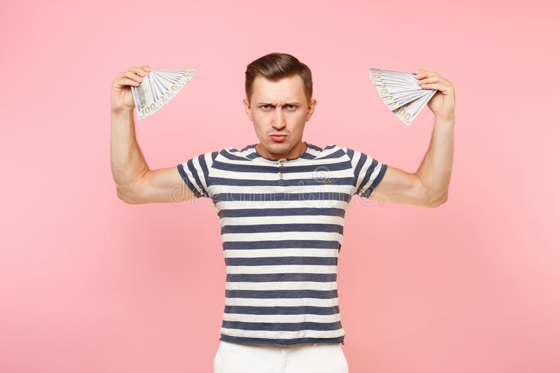 Portrait of smiling excited young man in striped t-shirt holding bundle lots of dollars, cash money, ardor gesture on. Copy space isolated on pink background royalty free stock photos